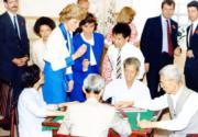 1989年11月,戴安娜(第二排左)探訪時,遇見長者打麻將。(資料圖片)