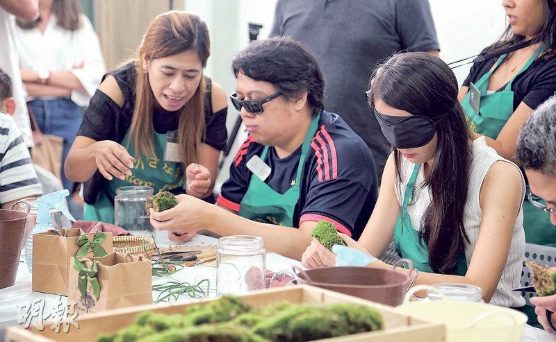 這是普通人和視障人士一起學習製作微型盆景的工作坊。圖中的導師(左)就是一名基層媽媽。