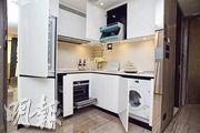 開放式廚房加設不少儲物空間,例如在吊櫃內加設拉下式層架,方便存取物件。(攝影 黃志東)