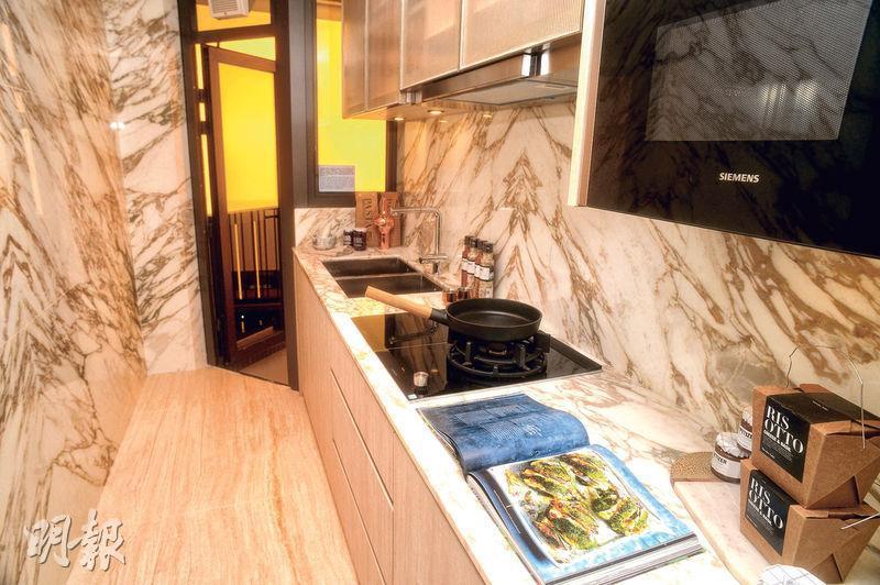 長形廚房放置淺木色廚櫃,備有明火煮食爐,外連16方呎工作平台。