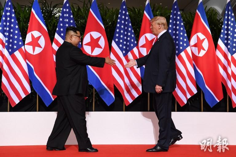 兩人今早在新加坡首度見面,雙方歷史性握手。(法新社)