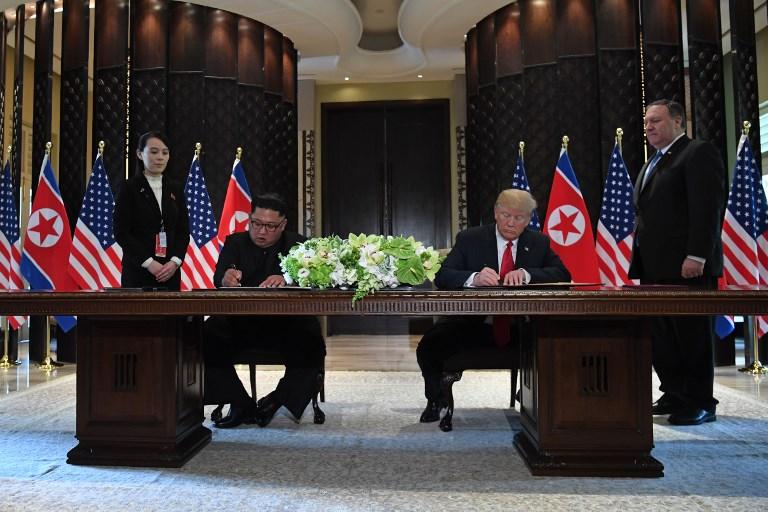 特朗普(右)與金正恩簽署文件。(法新社)