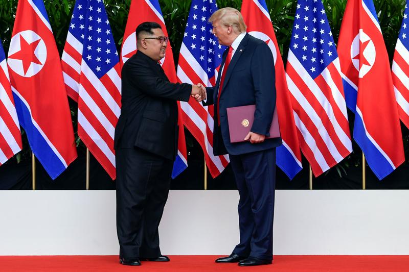 特朗普(右)與金正恩簽署及交換文件後握手,兩人均面露笑容。(路透社)