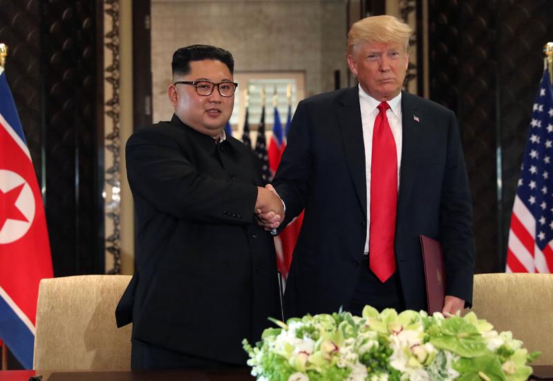 特朗普(右)與金正恩(左)簽署文件前後都多次握手。(路透社)