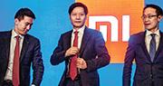 雷軍(中)表示,小米是一家全能型企業,同時從事電商、硬件和互聯網,是罕有的全能型企業,更可能是一個「新物種」。左為小米高級副總裁兼首席財務官周受資,右為另一創辦人林斌。(法新社)