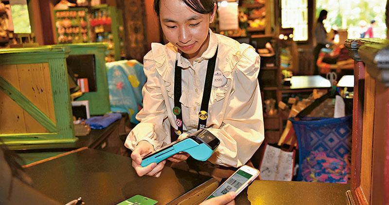 有調查顯示現金及八達通仍是港人過去一年最常用的支付工具,有使用手機支付的比例僅得兩成。圖為香港迪士尼樂園禮品店收銀員協助顧客使用手機微信支付。(中新社)
