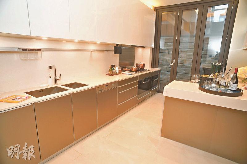 客飯廳的另一邊為廚房,設有長形工作枱和吧枱,同時亦裝有玻璃趟門,通往戶外花園。(攝影 劉焌陶)