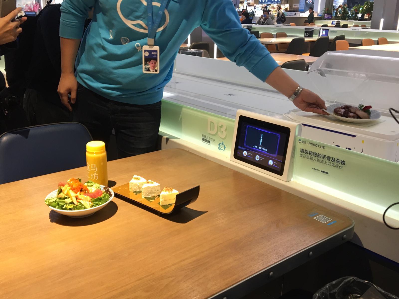 工作人員示範拿取機械人送達的食物。(蕭嘉聰攝)