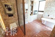 主人套房浴室以玻璃浴屏分隔座廁及淋浴區域,並設有浴缸。(李紹昌攝)