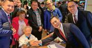 98歲婆婆鄧碧雲(前排左)去年底購入觀塘新盤凱滙單位時,獲信置副主席黃永光(右一)、營業部聯席董事田兆源(右二)款待及握手。(資料圖片)