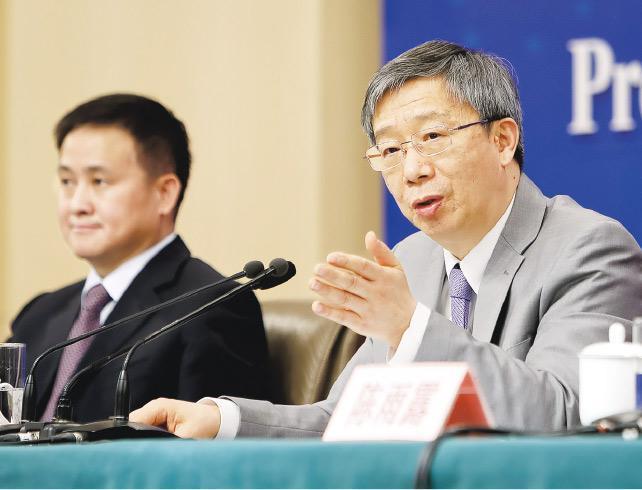 易綱(右)首度以人行行長身分主持全國兩會記者會,表示中國目前還有空間下調存準金率,但比前幾年可降準空間較小。旁為副行長潘功勝。(中通社)