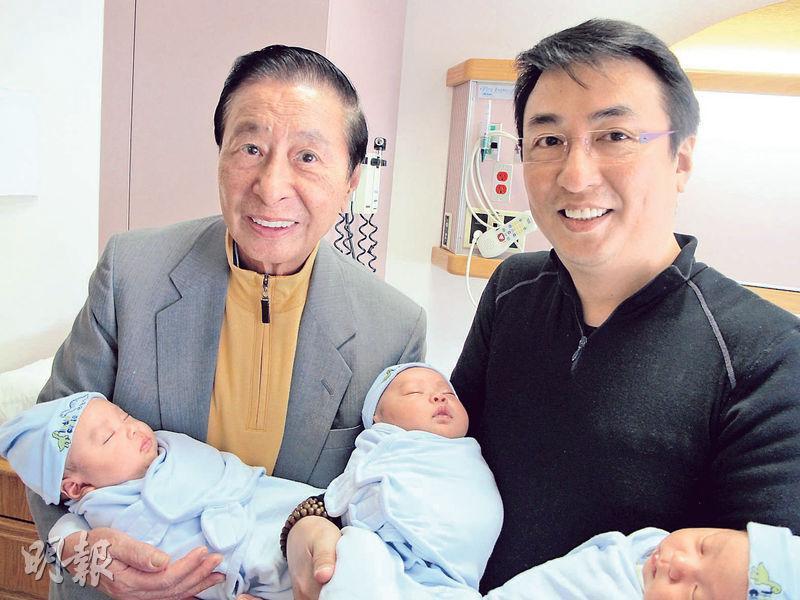 李兆基(左)長子李家傑(右)在美國找代母,一索得三男,圖為李兆基當年開心抱孫。(資料圖片)