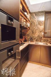 大門旁邊為梗牆間隔廚房,採U形工作枱設計,配備Gaggenau煮食爐具等。(劉焌陶攝)