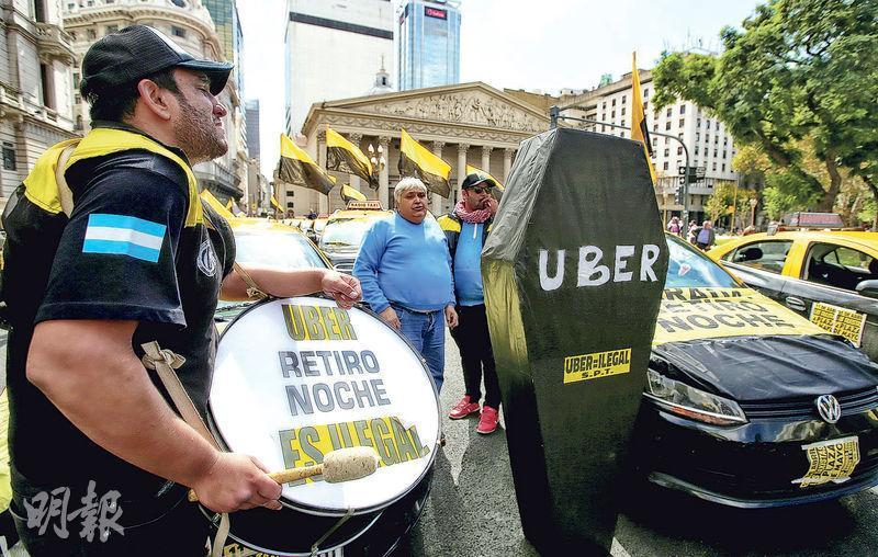 Uber進入新市場經常惹來爭議。阿根廷布宜諾斯艾利斯上周舉行抗議Uber的活動,司機在Uber紙板棺材旁邊演奏鼓,抗議Uber非法營運。(路透社)