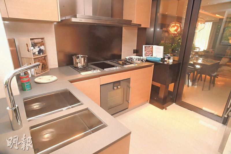 廚房設有曲尺工作枱,備有抽油煙機、煮食爐等品牌家電。(劉焌陶攝)