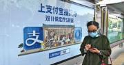 螞蟻集團首日招股反應熱烈,面對多家銀行推出優惠搶客,多家主要券商昨日仍獲大量客戶認購申請。圖為北京巴士站支付寶廣告。(法新社)