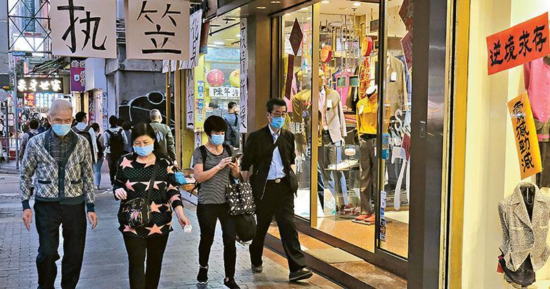 香港零售管理協會指出,香港爆發第四波疫情後,人流及生意動力隨即減弱,有逾半受訪會員預計明年首季將會關店節省成本。圖為佐敦零售店,部分掛出「執笠」大字報。(中通社)