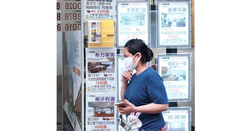疫情下,由於低息環境持續及住屋需求強勁,二手交投持續暢旺。圖為市民行經地產代理舖門前。(資料圖片)