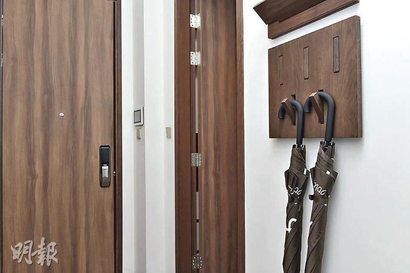 大門附近牆身放置木製掛鈎工具,方便掛起雨傘等出門用品。(朱安妮攝)