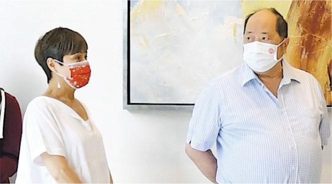 立法會議員張華峰(右)昨現身晉環展銷現場,他表示人太多,只有太太(左)參觀示範單位。(劉焌陶攝)
