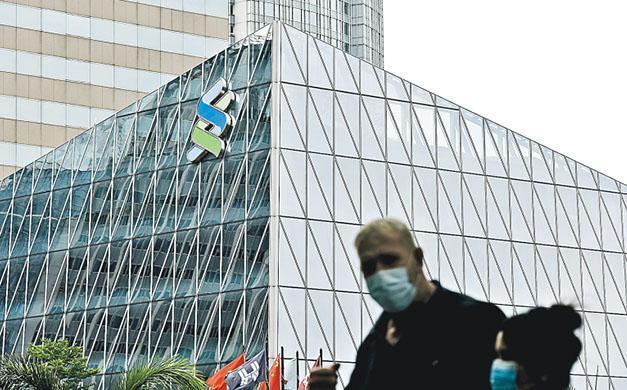 渣打近月已削減香港中環及觀塘的辦公室面積,早前亦有外媒報道,渣打已減少新加坡總部所在濱海灣金融中心的辦公室。圖為市民經過香港中環一家渣打銀行。(中通社)