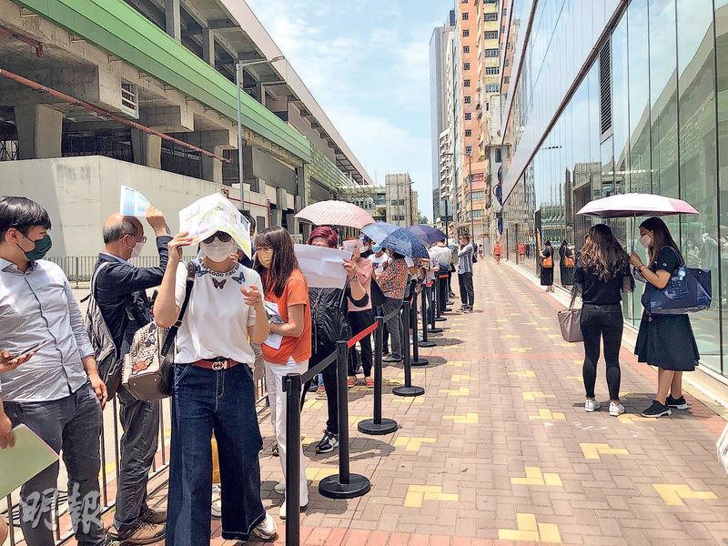 黃竹坑晉環準買家人數眾多,加上社交隔離限制,不少準買家要在室外排隊等候,部分人戴上太陽眼鏡及撐傘遮陰。