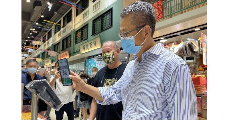 陳茂波昨日到訪一個街市購物時,使用WeChat Pay HK支付。(網誌圖片)