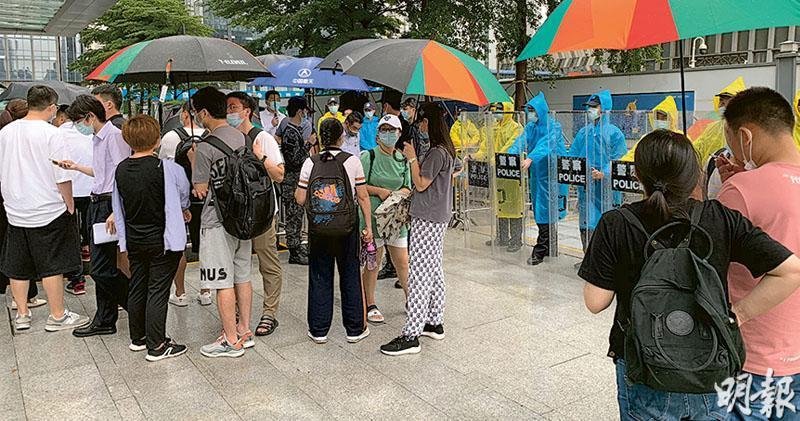 恒大深圳總部卓越後海中心昨再有數十名商票持有人冒雨索賠,表明不接受任何方案,警方介入維持秩序。(明報記者攝)