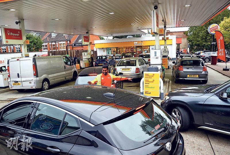 英國「脫歐」後,大量來自歐盟的司機離開,由於缺乏司機運送物資,英國油站連日大排長龍。圖為倫敦一油站,職員正指示汽車分流進入加油。(路透社)