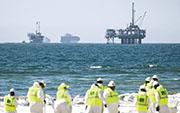 全球能源供應緊張,紐約期油昨曾升穿每桶82美元。圖為上周加州一個鑽油台發生漏油事故,工人在沙灘清理油污。(法新社)
