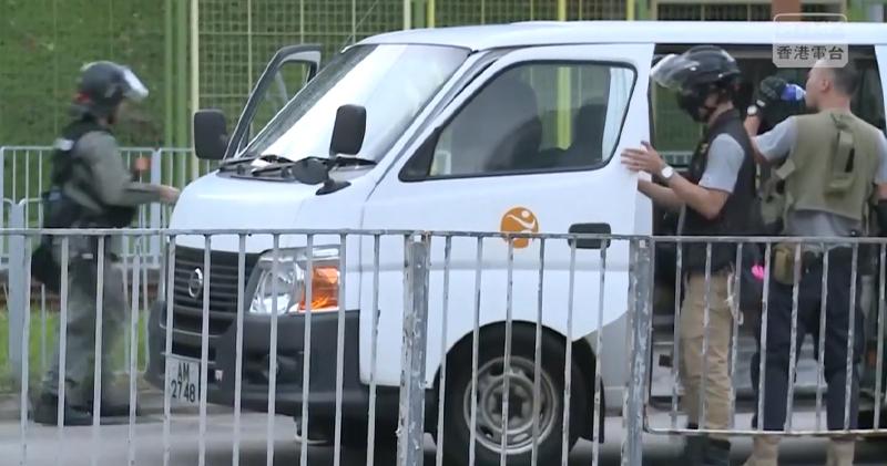 今午有警員駕駛一輛印有康文署標誌的白色客貨車到屯門,其後下車制服示威者。(香港電台影片截圖)