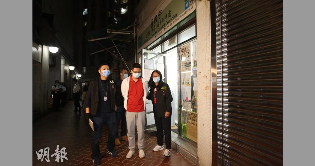 屯門區議員盧俊宇(白外套者)被捕,晚上被押到其議員辦事處蒐證。(伍浦鋒攝)