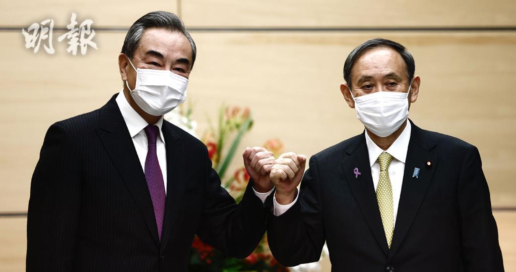 日本首相菅義偉(右)與訪日的中國國務委員兼外長王毅(左)會晤。(法新社)