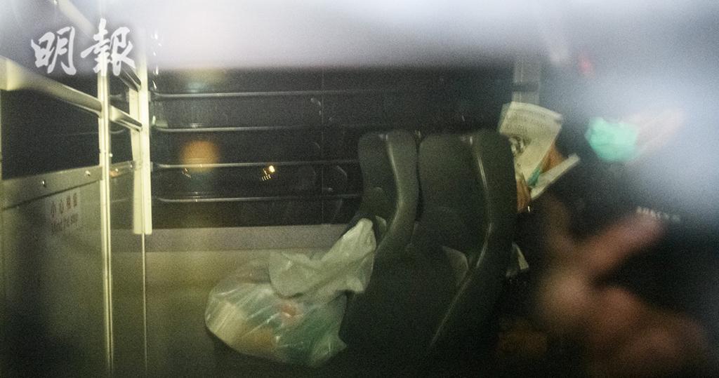 張祺忠在囚車駛離法院時以報紙遮面。(林靄怡攝)