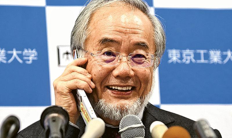 大隅良典昨在記者會接到日本首相安倍晉三的祝賀來電,他笑着和對方講電話。(路透社)