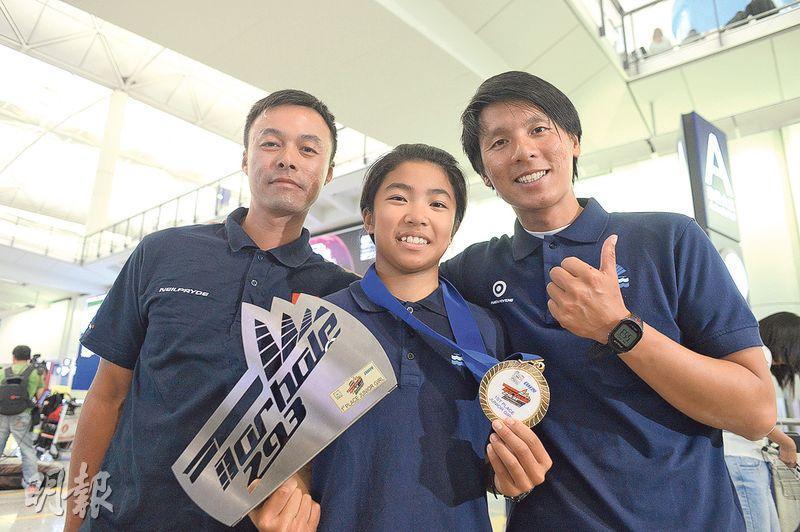 麥卓穎(中)昨凱旋,不忘歸功教練鄭慶麟(左)和鄭國輝(右)於比賽時從旁指導。(鍾林枝攝)
