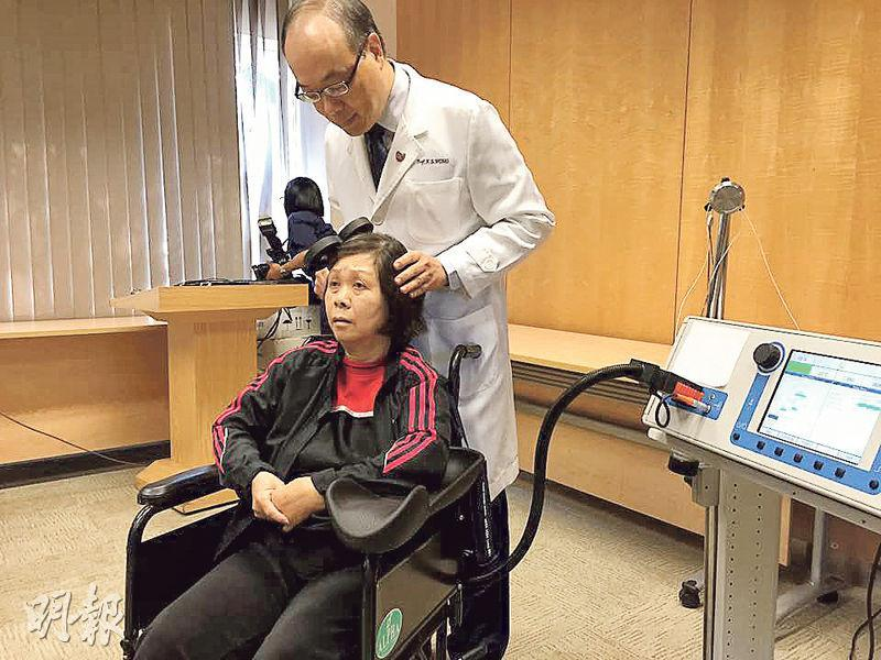 中大醫學院研究中風康復療法,專家黃家星(白袍者)稱,使用腦磁激儀器(圖右)刺激腦細胞活動,配合體外反搏法及物理治療,希望助病人恢復上肢活動能力。圖為曾接受有關療法的病人余女士。(劉嘉裕攝)