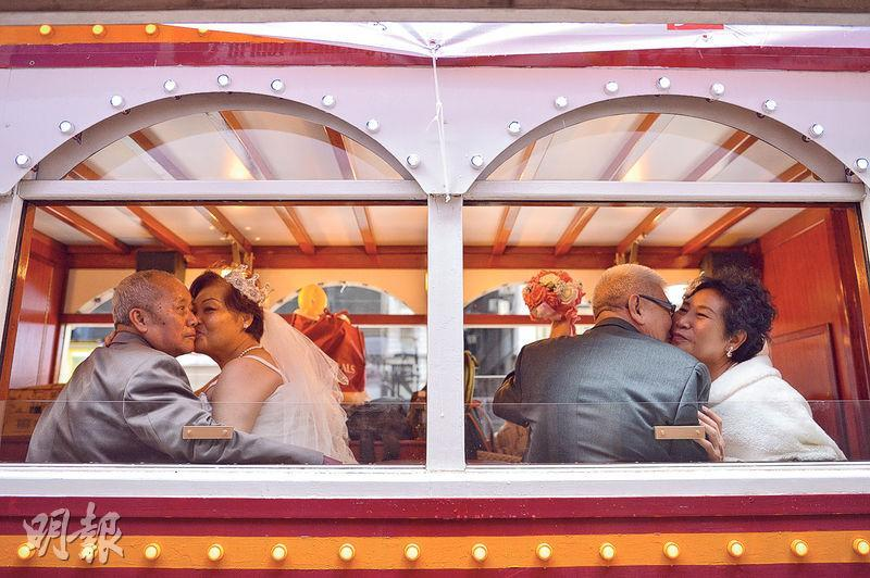無國界義工噚日為19對銀髮「新人」舉辦「跨世紀長者婚禮」,佢哋行完禮就搭電車穿梭港島,踏入金婚之年嘅林先生夫婦(右)仲不時深情擁吻曬浪漫,羨煞途人。(蘇智鑫攝)