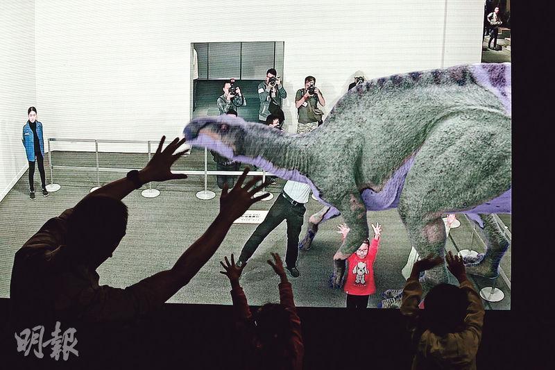 「超感官暴龍展」將虛擬恐龍帶到參觀者眼前,例如圖中嘅「回到侏羅紀」展品,參觀者就可以喺大型屏幕前同恐龍「互動」。(李紹昌攝)