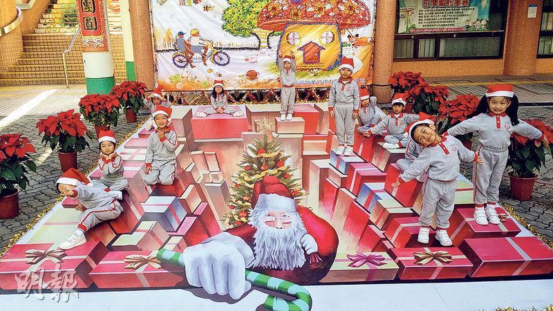 元朗水邊圍邨嘅立體畫「聖誕盒子」有好多個禮物盒,聖誕老人喺地下爬上嚟。(政府新聞處)
