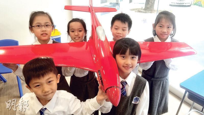 德萃小學下月開展飛機建造計劃,30名初小學生將在導師指導下,在校園裏參與製造一架4米乘4米的大型定翼無人偵察機。圖為該校學生抬着飛機的模型。(鄧力行攝)