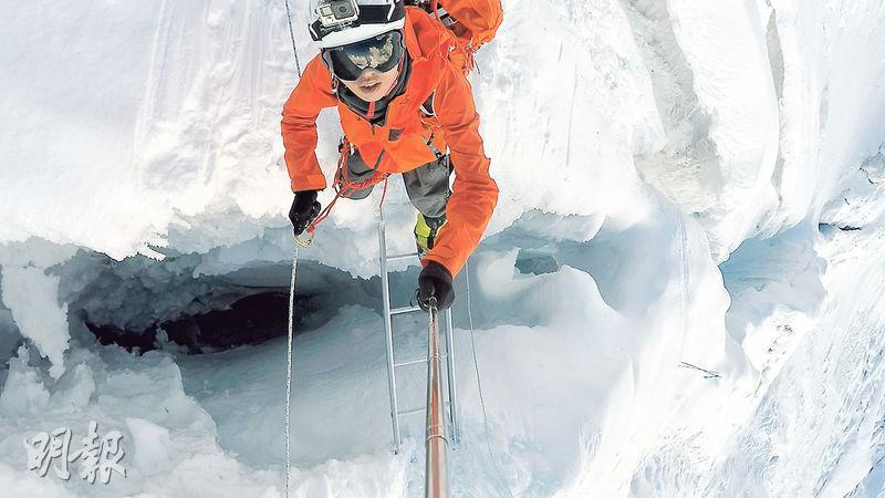 自拍跨冰隙——登頂前,Elton要跨過幾百次這樣的冰隙,腳下是萬丈深淵。細心看看,他手持「神棍」自拍,頭頂還有一部Go Pro!(圖:受訪者提供)