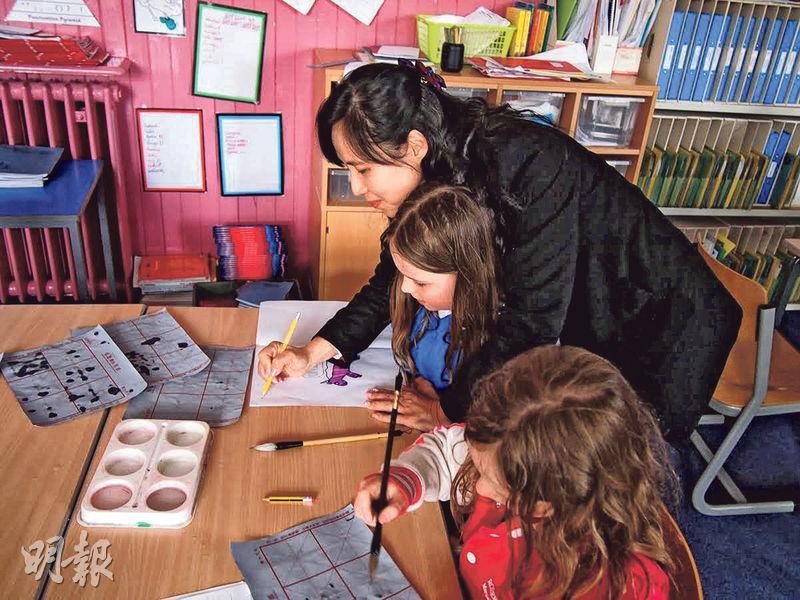 10多名中小學教師去年到蘇格蘭觀課,了解當地學校如何實踐自主學習。圖為「團友」油蔴地天主教小學校長余佩琴教導當地學生寫中文字。(教師馮朗提供)