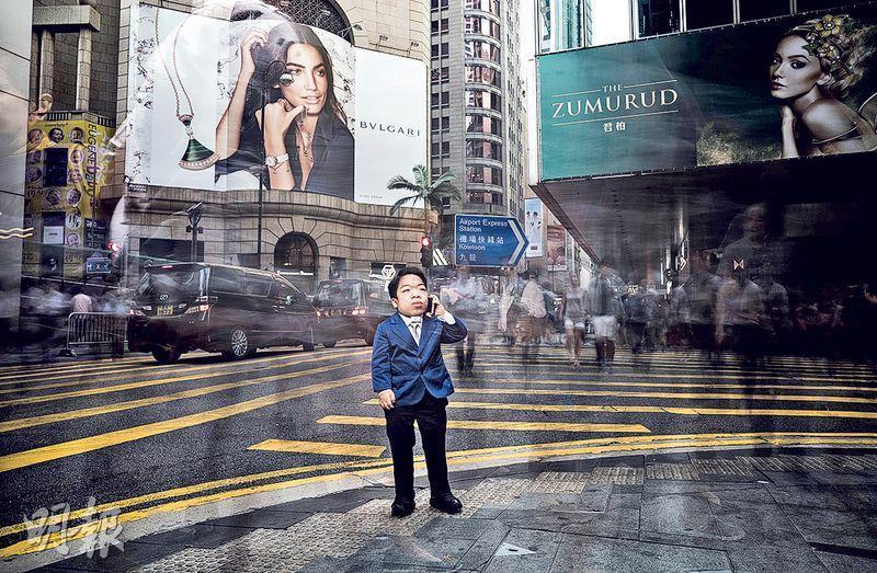 馬歷生性格開朗,夢想成為「中環上班族」,攝影師Stephen Cheung於是為佢設計「Big Boss」造型,著西裝喺中環街頭留影。(香港黏多醣症暨罕有遺傳病互助小組提供,Stephen Cheung攝)