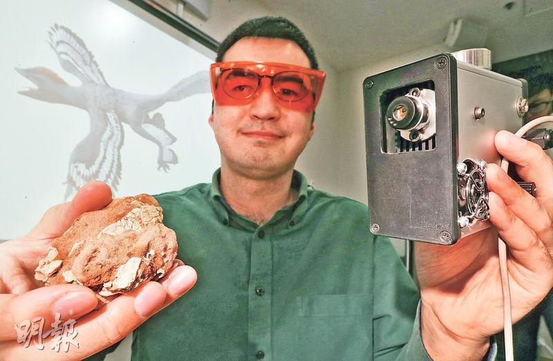 港大地球科學系研究助理教授文嘉棋(圖)利用激光誘導熒光技術儀器(圖右)掃描近鳥龍化石(圖左),追查近鳥龍是否能飛之謎。(李紹昌攝)