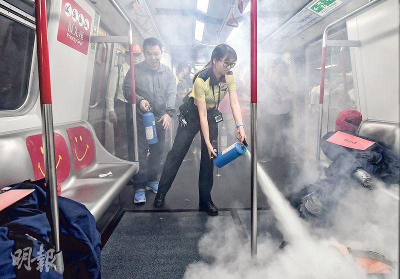 港鐵舉行聯合緊急事故演習,模擬一列行駛中列車有乘客攜帶的物品着火造成22人受傷,由職員與乘客持滅火筒入車廂將火救熄,消防員則「救出」22名傷者急救及送院治理。(港鐵提供)