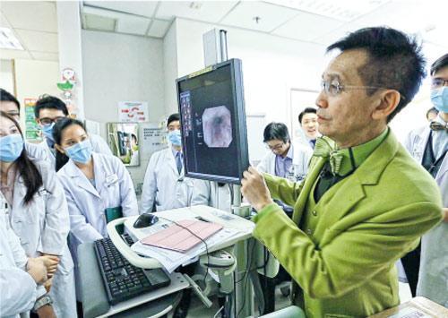 68歲的港大醫學院內科學系講座教授黎青龍(右)打扮時尚,在節目中以全身綠色的衣飾巡房,他說病人都喜歡見到他。(港台《大醫之道》片段撮圖)