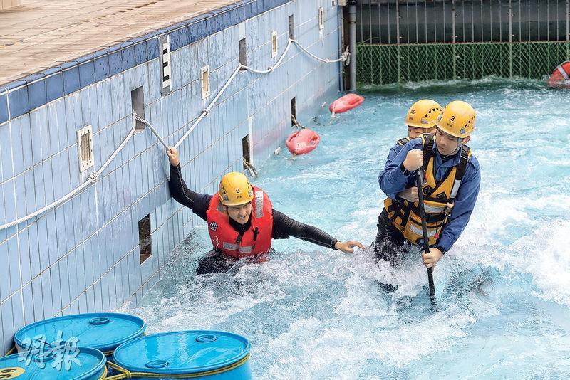 消防潛水基地的急流池可製造每秒流量1.5米的急流,模擬本港暴雨後的街道及潮漲石澗,池中的膠桶製造真實環境中的「回流區」,令場景更逼真。隊員在此情况下,練習兩人一組(右)涉水救人。(李紹昌攝)