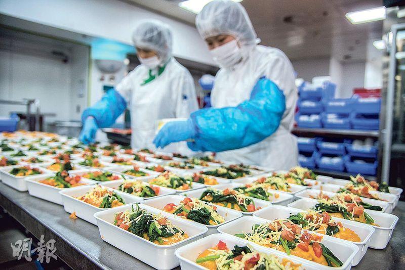 擺盤步驟——員工仔細把食物分配到各個餐盒上,擺得整齊美觀。(圖:黃志東)