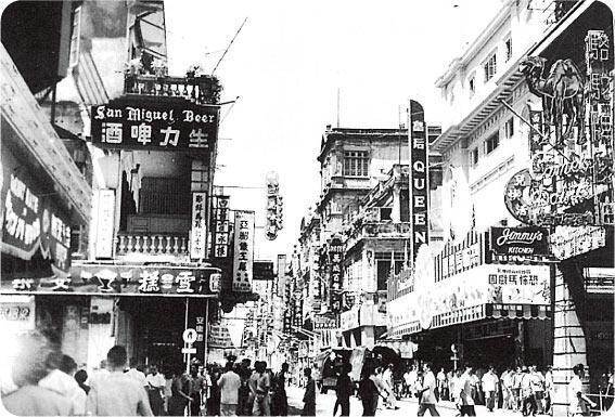 香港冰室——約一九五二年位於皇后大道中的安樂園飲冰室(左),以雪糕最馳名;右方的華人行可見本地老牌西餐廳Jimmy's Kitchen的招牌。(圖片出處:鄭寶鴻《香江知味:香港的早期飲食場所》)